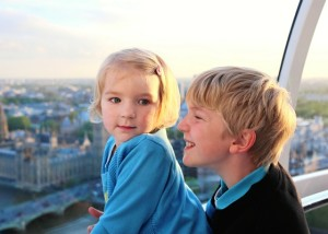 Family with young children enjoying trip to UK. Kids looking through the window of London Eye wheel. Beautiful view on London's southern part: cityscape, Westminster Abbey, Big Ben and Thames river